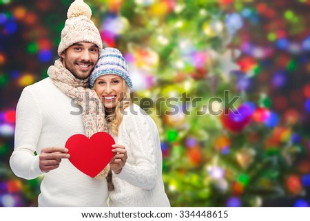 love, valentines day, couple, christmas and people concept - smiling man and woman in winter hats and scarf holding red paper heart shape over holidays lights background - stock photo