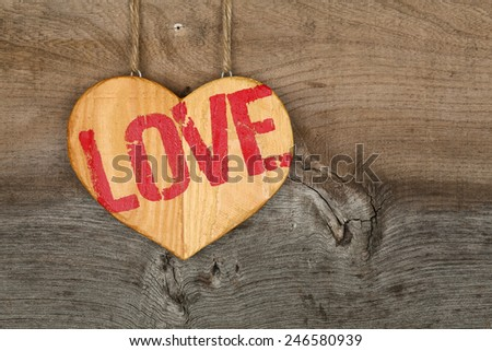 Love Valentines message wooden heart sign from recycled old palette on rough grey wood background, copy space