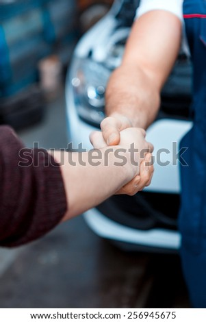 Love what I do. Closeup portrait of a handshake of a car mechanic and his client in the car repair station - stock photo