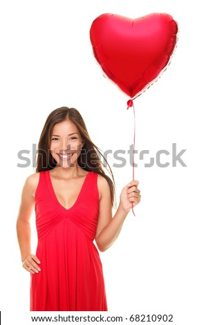 Love woman smiling holding red heart shaped balloon. Cute beautiful young woman in love. Asian / Caucasian female model in red dress isolated on white background. For Valentines day concepts etc.