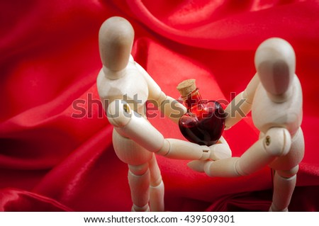 Love wooden figurines on silk red background holding a heart shaped blood vial. Vintage chic style. Soft warm tender feelings. Holiday card for valentine's day. - stock photo