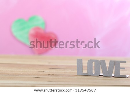 Love word by paper cutting with heart on pink background - stock photo