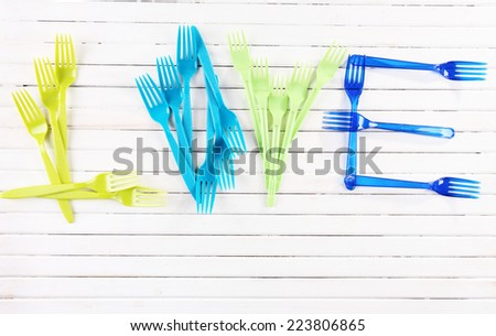 Love word formed with plastic disposable tableware on wooden background - stock photo