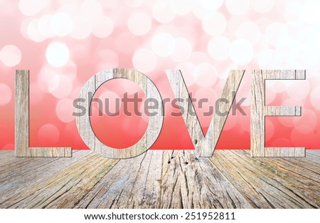 love word in wood texture on wooden table with pink bokeh background - stock photo