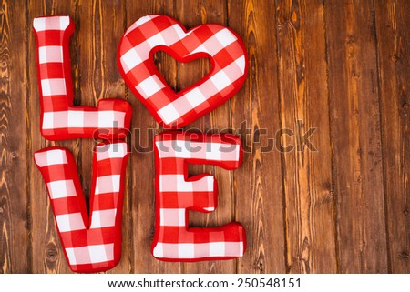 Love word of plush red letters on wood background. Full plaid textile. February 14, Valentine's Day concept shot with text space. Top view. High resolution - stock photo