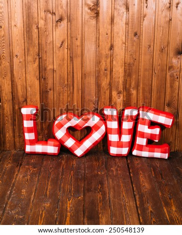 Love word of plush red letters on wood corner background. Full plaid textile. February 14, Valentine's Day concept shot with text space. Top view. High resolution - stock photo