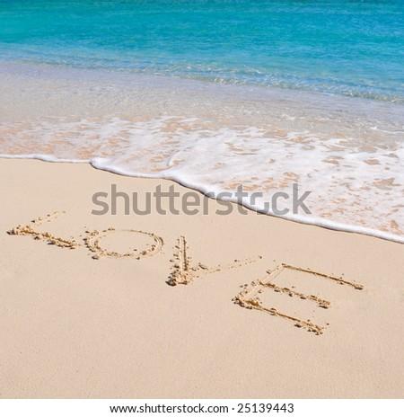 Love written in a sandy beach - stock photo