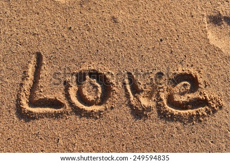 Love written in the sand on the beach - stock photo