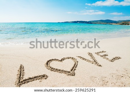 love written on a tropical beach under clouds