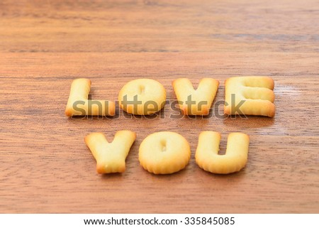love you alphabet biscuit on wooden table, stock photo - stock photo