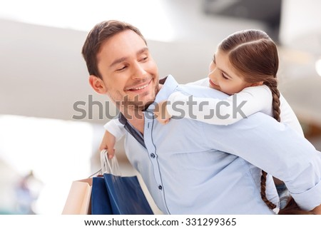 Love you so much. Pleasant positive handsome loving father holding his daughter on the back and having fun while shopping in   a mall - stock photo