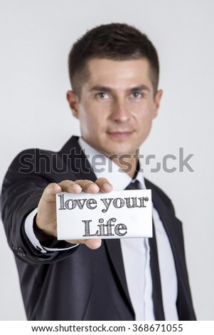 love your Life - Young businessman holding a white card with text - vertical image