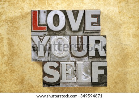 love yourself phrase made from metallic letterpress type on grunge cardboard background