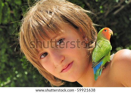 Lovebird parrot on the shoulder of a happy young girl. - stock photo