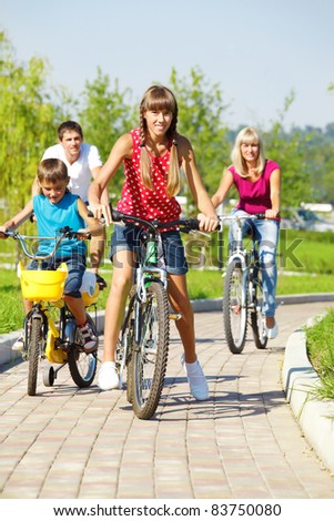 Lovely active family of four riding bicycles in park - stock photo