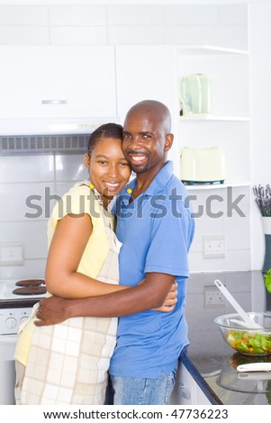 lovely african american couple embracing in kitchen