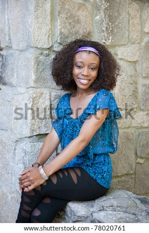 Lovely African American woman sitting against stone wall