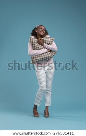Lovely african woman holding and embracing pillow on blue background - stock photo