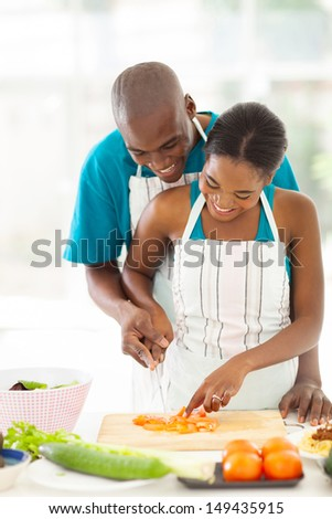 lovely afro american couple chopping tomato together in kitchen - stock photo