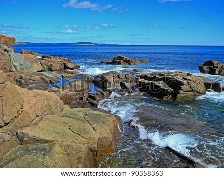 Lovely and dramatic landscape showing the tide rolling in among boulders of the scenic, rocky Acadia coastline at Thunder Hole. - stock photo