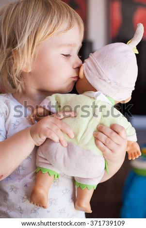 lovely and tender scene of blonde caucasian cute baby two years old kissing on the cheek or talking to ear a doll in hands indoor - stock photo