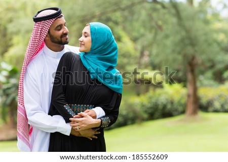lovely arabian couple embracing outdoors - stock photo