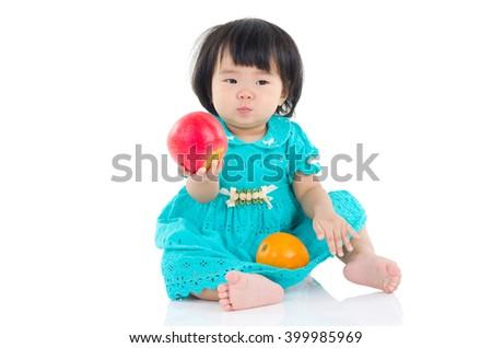 Lovely asian baby girl eating apple and orange - stock photo