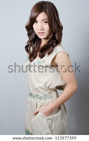 Lovely Asian model girl posing on gray background - stock photo