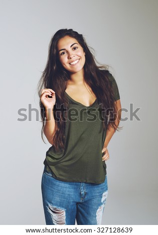 Lovely attractive young woman with a warm friendly smile wearing ragged designer jeans and a casual t-shirt standing looking at the camera - stock photo