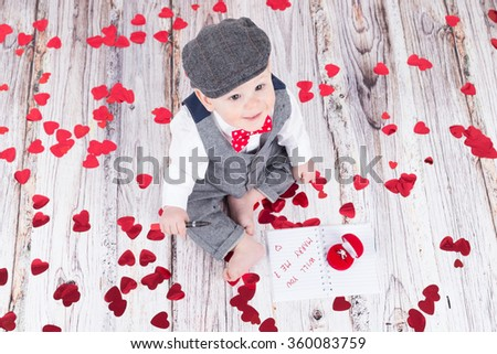 lovely baby boy in barret sitting with betrothal ring - stock photo