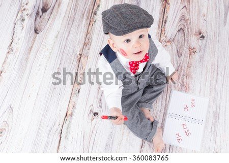 lovely baby boy in barret with lipstick kiss on his cheek - stock photo