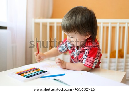 lovely baby boy painting with wax pencils at home