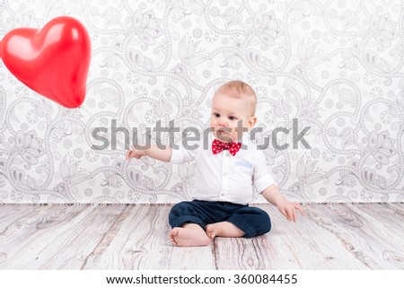 Lovely baby boy playing with red heart shaped balloon - stock photo