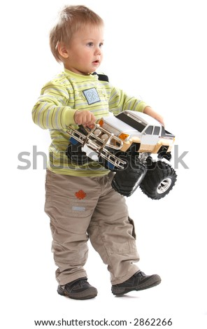 Lovely Baby Boy playing with toy monster truck shot in studio