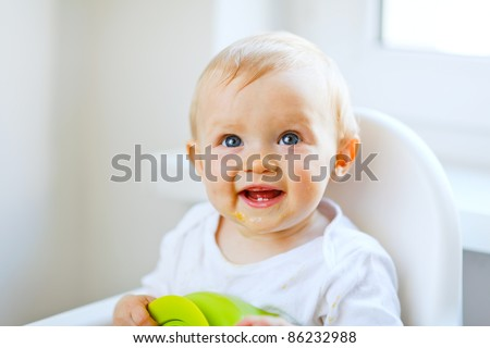 Lovely baby girl sitting in baby chair - stock photo
