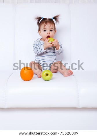 Lovely baby girl sitting on the sofa and eating fruit - stock photo
