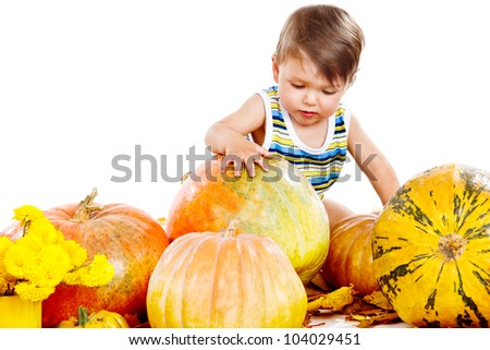 Lovely baby playing with large pumpkins