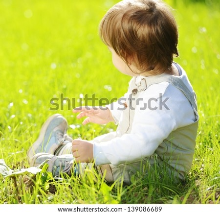 Lovely baby sitting on the green grass in the park and smiling for summer happy days - stock photo