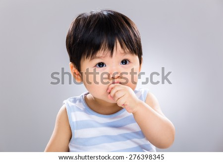 Lovely baby son eating with cookie - stock photo