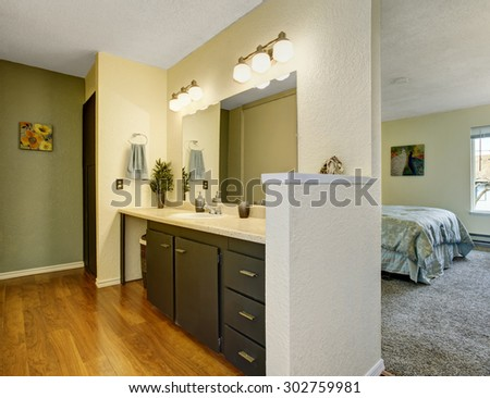 Lovely bathroom joined with master bedroom with hardwood floor, and a large mirror. - stock photo