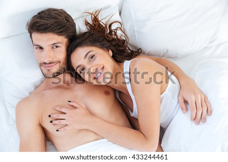 Lovely beautiful couple hugging on their bed at home - stock photo
