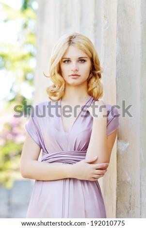 lovely beautiful girl standing near the column - stock photo