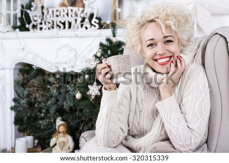 Lovely big smile blonde woman sitting in the cozy comfort of home chair with a blanket wearing a knitted sweater jersey. Series of christmas, x-mas, new year, winter celebration theme photos.  - stock photo