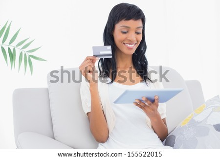 Lovely black haired woman buying online with her tablet pc in a living room - stock photo