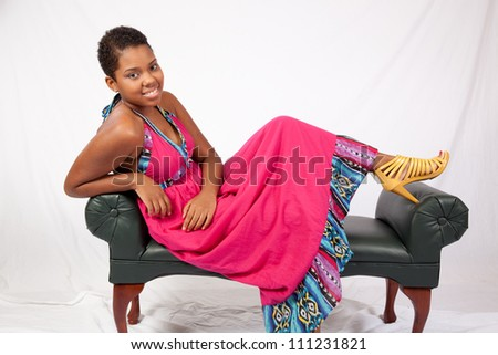 Lovely black woman in a red dress, playfully reclining on a bench with eye contact to the camera and a friendly, happy smile, in a relaxed pose - stock photo
