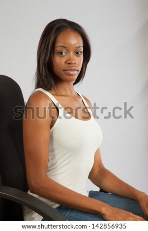 Lovely black woman in a white, tank top, sitting in a executive chair, and looking at the camera with a calm, but serious, pensive  expression