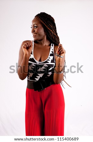 Lovely black woman in red pants, standing looking to the left with happy, friendly smile - stock photo