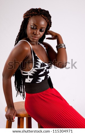 Lovely black woman in red slacks sitting on a wooden stool with a thoughtful and friendly expression on her face - stock photo