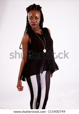 Lovely black woman in striped pants, standing looking at the camera with a playful but serious expression - stock photo
