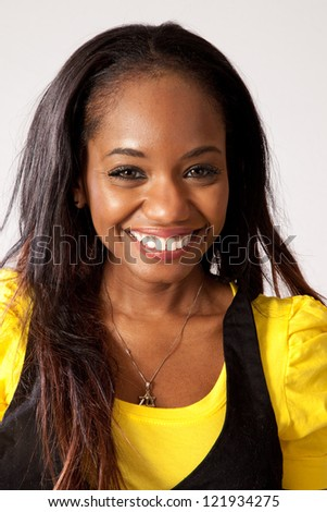 Lovely black woman in yellow shirt and black vest,   with eye contact to the camera and a big, happy and friendly smile